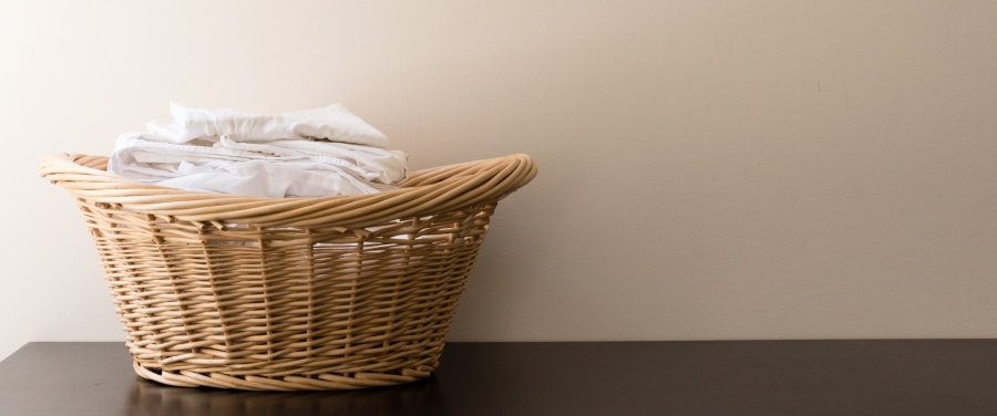 Wicker laundry basket with folded white washing on black table against wall